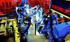 robots arc welding in a manufacturing plant